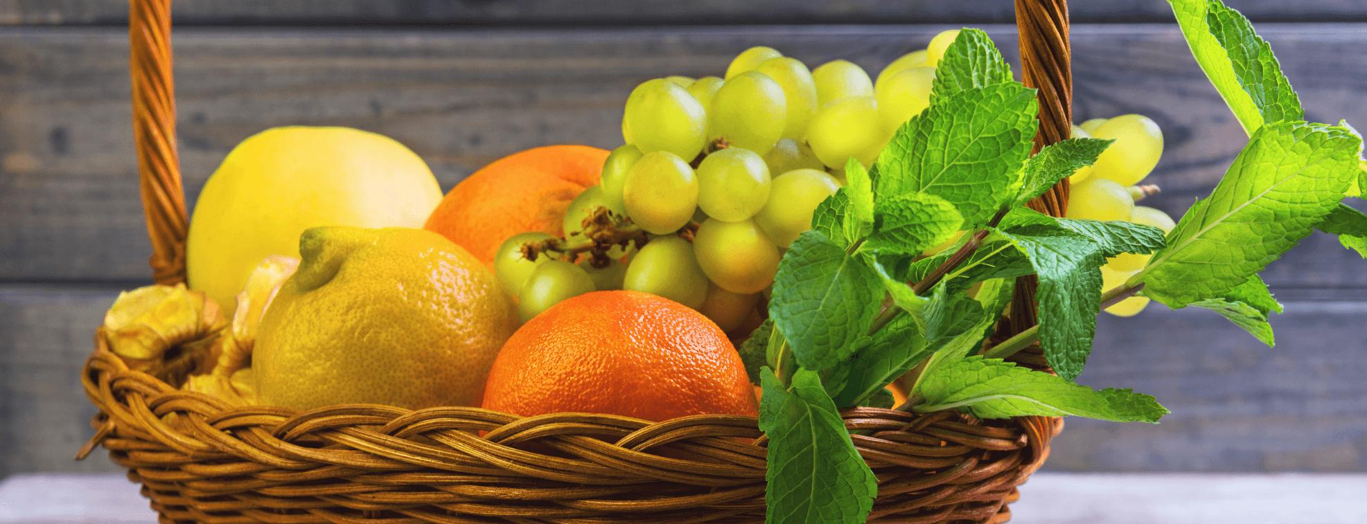 Apples, tangerines, grapes, lemons and other round fruits in a basket