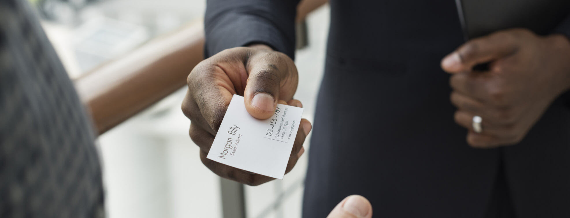 Man handing a high-quality business card to another person