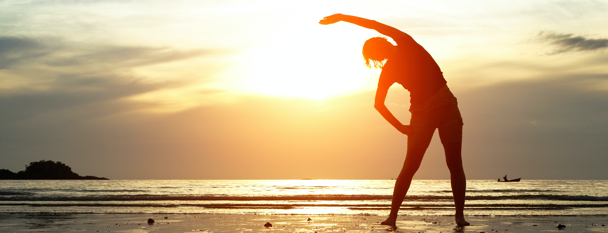 A woman exercising while looking at a sunset
